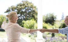 Senior caucasian couple dancing on patio — Stock Photo