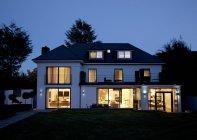Moderna casa iluminada à noite — Fotografia de Stock