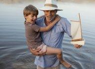 Sorridente nonno e nipote con barca a vela giocattolo guadare nel lago — Foto stock