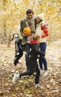 Casal com crianças em trajes de esqueleto no parque — Fotografia de Stock