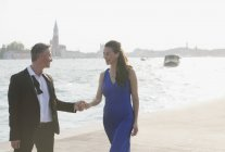 Coppie well-dressed che tengono le mani al waterfront a Venezia — Foto stock