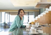 Woman talking on cell phone in kitchen — Stock Photo