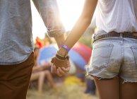 Paar hält Händchen bei Zelten bei Musikfestival — Stockfoto