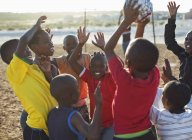 African boys playing soccer together in dirt field — Stock Photo