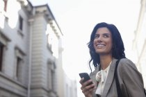 Happy businesswoman text messaging with cell phone — Stock Photo