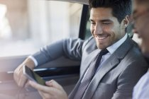 Businessmen looking at cell phone in car — Stock Photo