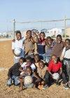 Afrikanischen Jungen Fußbälle in Schmutz Feld hält — Stockfoto