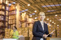 Businesswoman using clipboard in warehouse — Stock Photo