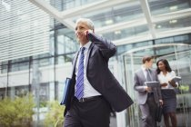 Businessman talking on phone while walking out of office building — Stock Photo