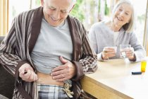 Older man giving himself injection — Stock Photo