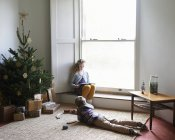 Caucasian happy children relaxing by Christmas tree — Stock Photo