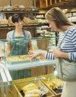 Mujer de compras en el mostrador de delicatessen en tienda de comestibles - foto de stock