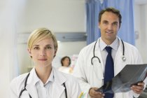 Doctors standing in hospital room and looking at camera — Stock Photo