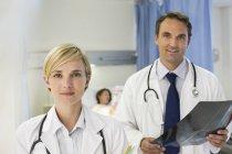 Ärzte stehen im Krankenhauszimmer und schauen in die Kamera — Stockfoto
