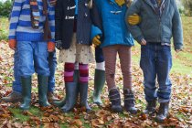 Crop children standing together in autumn leaves — Stock Photo