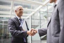 Бизнесмены пожимают руки в офисном здании — стоковое фото