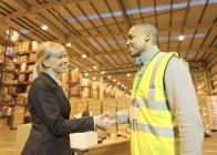 Предприниматель и работника, пожимая руки на складе — стоковое фото