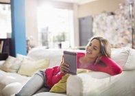 Mujer usando tableta digital en sofá - foto de stock