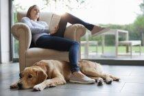Собака сидит с женщиной в гостиной — стоковое фото