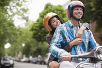 Couple riding scooter together outdoors — Stock Photo