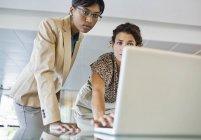 Geschäftsfrauen nutzen gemeinsam Laptop im modernen Büro — Stockfoto