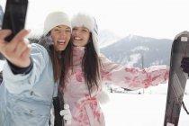 Femmes enthousiastes avec skis prenant Autoportrait avec appareil photo de téléphone dans le champ — Photo de stock