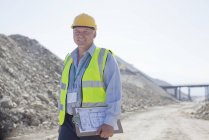 Businessman carrying clipboard in quarry — Stock Photo