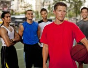 Group of athletic men standing on basketball court — Stock Photo