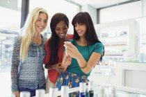 Women examining skincare products in drugstore — Stockfoto