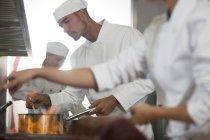 Cuochi che cucinano in cucina ristorante — Foto stock
