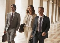 Smiling business people walking along corridor — Stock Photo