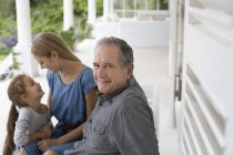 Happy older man smiling on porch — Stock Photo