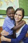 Вчитель і афро-американських студентів обіймає в класі — стокове фото