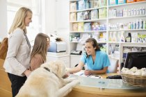 Recepcionista saudação cão em cirurgia veterinária — Fotografia de Stock