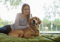 Mulher cão de estimação na cama na casa moderna — Fotografia de Stock
