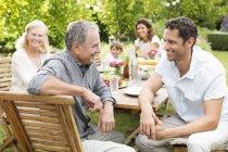 Multi-Generationen-Familie sitzt am Tisch im freien — Stockfoto