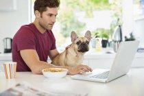 Mann am Laptop Petting Hund in Küche moderne zuhause — Stockfoto