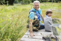 Man fishing with grandson on wooden dock — Stock Photo