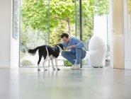 Homme souriant caressant chien dans la cuisine — Photo de stock