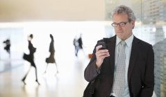 Businessman text messaging with cell phone in lobby at modern office — Stock Photo
