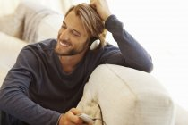 Young attractive Man listening to headphones on sofa — Stock Photo