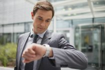 Businessman looking at watch outside office building — Stock Photo