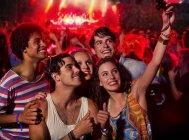 Amigos fazendo auto-retrato com telefone câmera no festival de música — Fotografia de Stock
