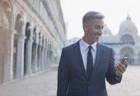 Sourire d'homme d'affaires contrôle cellulaire dans St. Marks place à Venise — Photo de stock