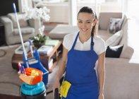 Geschickte kaukasische Dienstmädchen lächeln im Wohnzimmer — Stockfoto