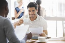 Businessman drinking coffee at meeting in cafe — Stock Photo