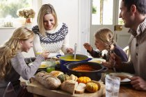 Happy family eating together at table — Stock Photo