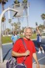Older man carrying gym bag on court — Stockfoto