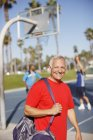 Older man carrying gym bag on court — Stock Photo