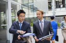 Businessmen talking outside of modern office building — Stock Photo
